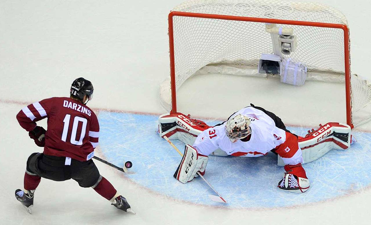Lauris Darzins of Latvia scores a goal against Carey Price of Canada in a game that was tied 1-1 late in the third period. The Canadians avoided the upset and won 2-1.
