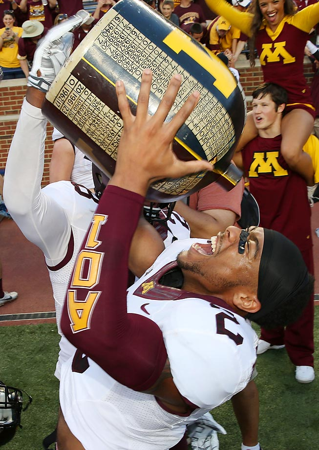 Cedric Thompson of Minnesota celebrates a win over Michigan with the Little Brown Jug.