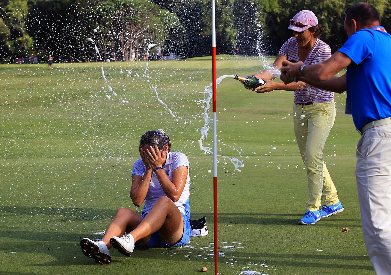 Celine Herbin gets sprayed with champagne after winning the Lacoste Open in France.