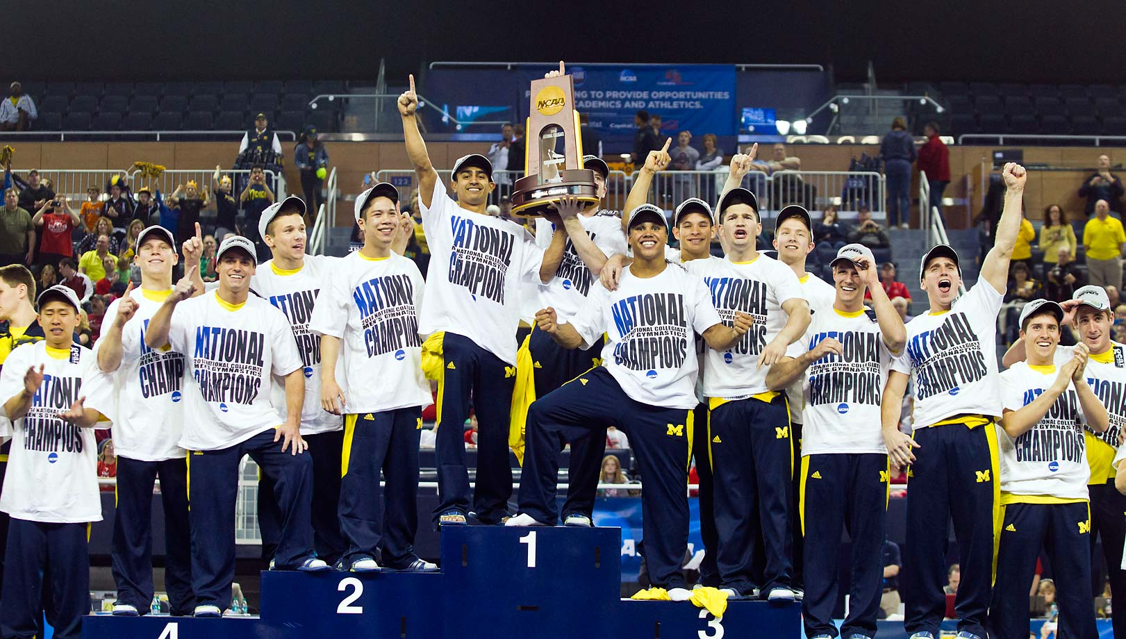 "Michigan's men's gymnastics squad poses on the podium after winning their sixth national title.  In their self-proclaimed ""Golden Era"", Michigan's men's gymnastics team has been dominant, as evidenced by their successful title defense (they won the title last year too)."