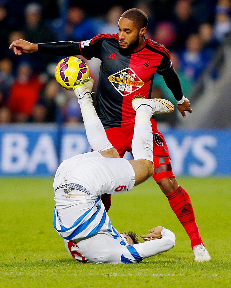 Charlie Austin of QPR and Ashley Williams of Swansea City battle for the ball during the Barclays Premier League match.