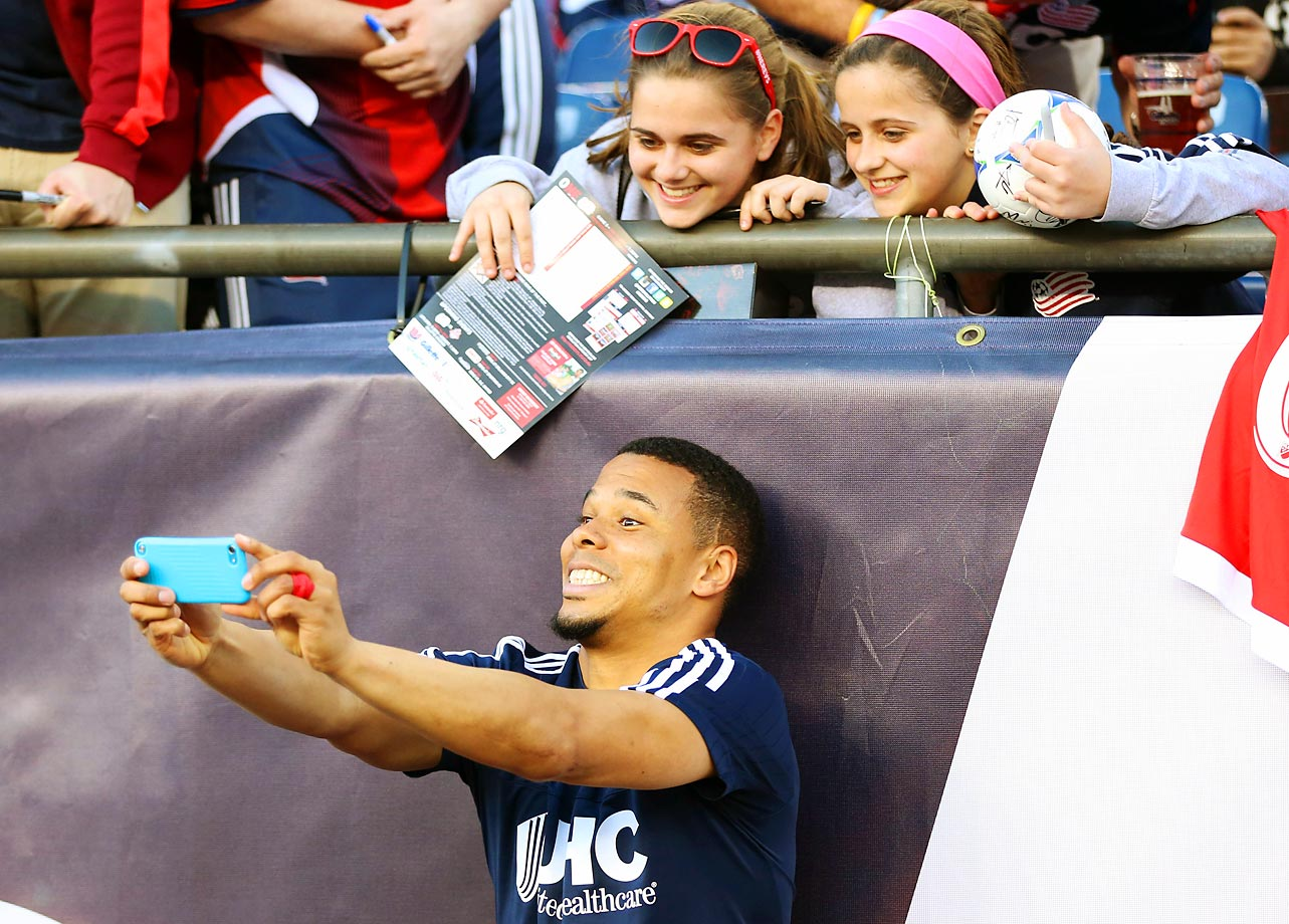 Charlie Davies of the New England Revolution takes a selfie with fans during a game against the Red Bulls at Gillette Stadium.