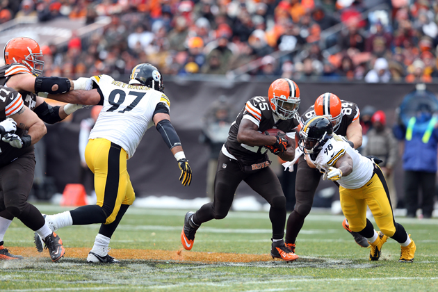 Cleveland Browns running back Chris Ogbonnaya (25) runs for a first down while being chased by Pittsburgh Steelers defensive end Cameron Heyward (97) during a game against the Pittsburgh Steelers on Sunday, Nov. 24, 2013 in Cleveland.