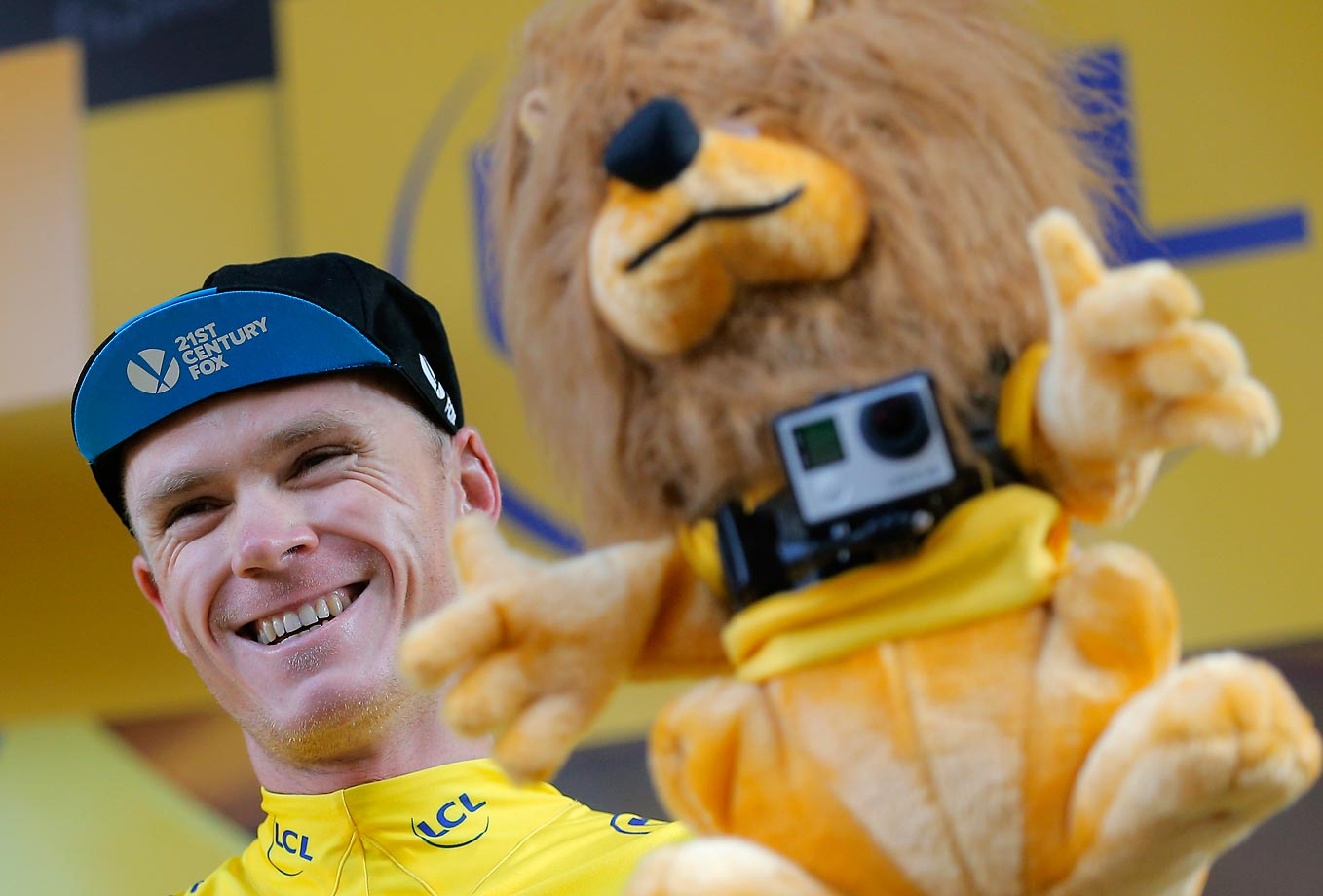 Chris Froome, wearing the overall leader's yellow jersey, is all smiles as he holds the yellow jersey's trophy equipped with a camera on the podium of the 16th stage of the Tour de France.