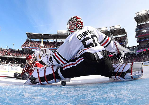 Blackhawks goalie Corey Crawford looks for the puck after stopping a shot.
