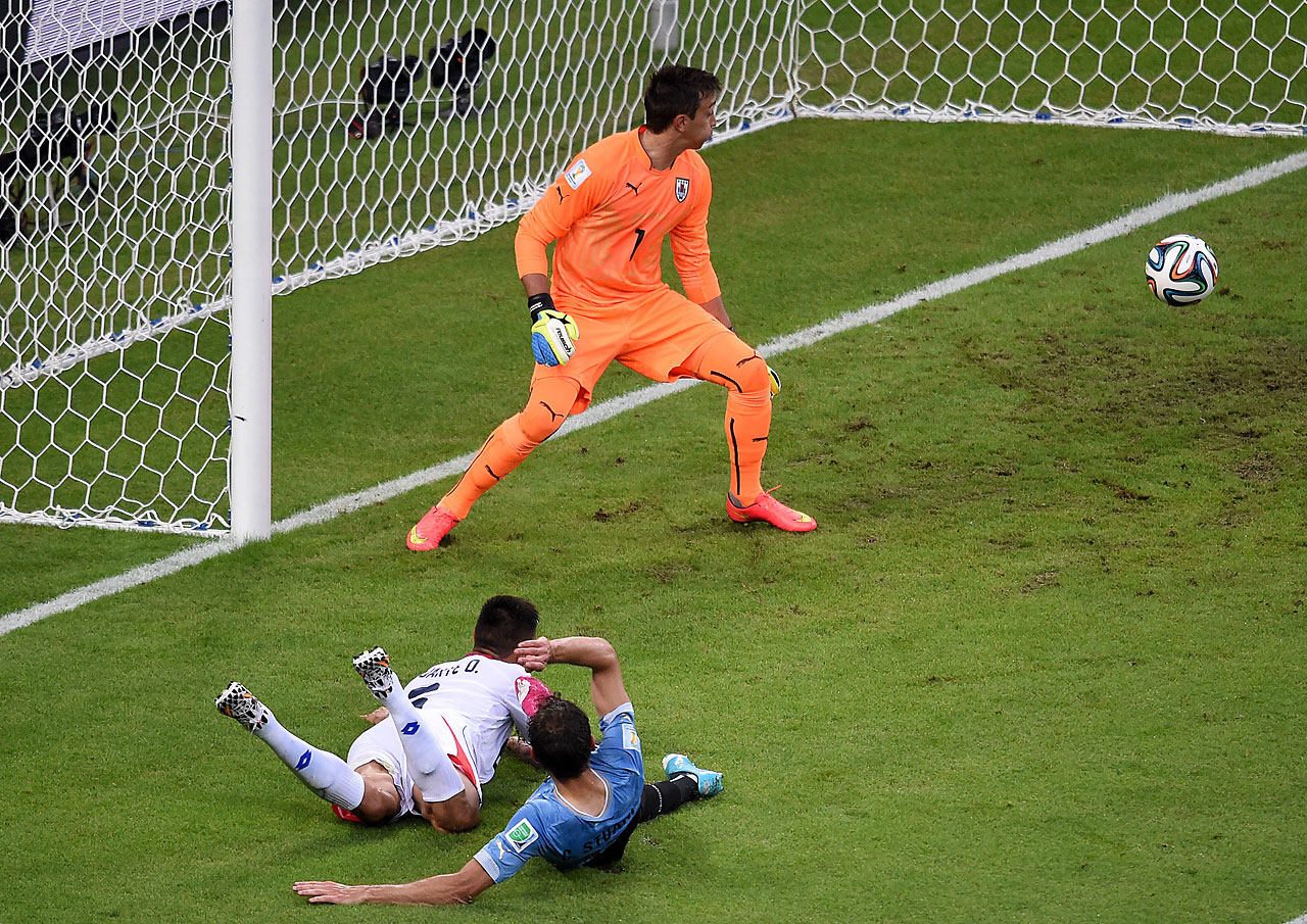 Costa Rica's defender Oscar Duarte  heads the ball past Uruguay's goalkeeper Fernando Muslera to score his team's second goal during a 3-1 win over Uruguay.