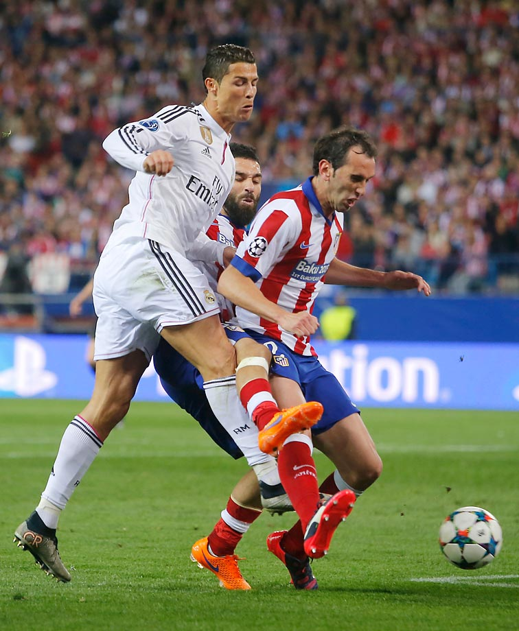 Cristiano Ronaldo, Diego Godin and Arda Turan get tangled up during the Champions League quarterfinal first leg soccer match between Atletico Madrid and Real Madrid.