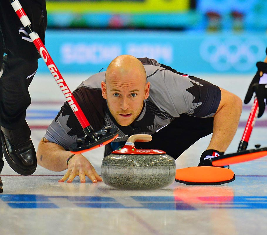 Ryan Fry of Canada handles the stone during the curling competition.