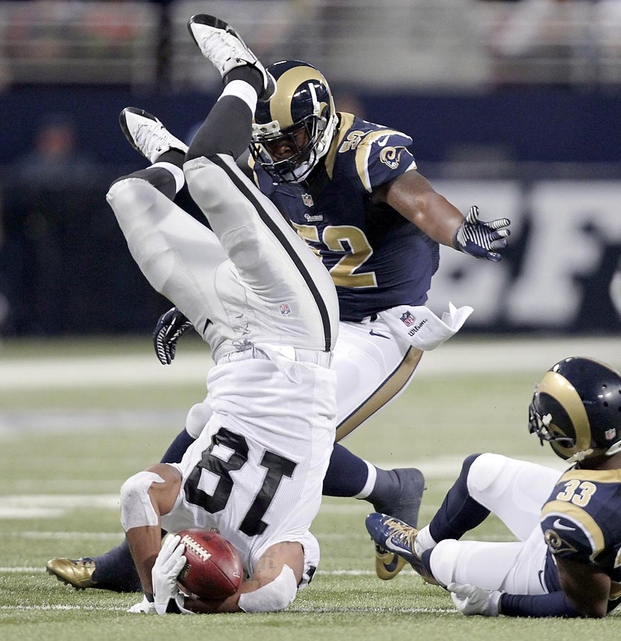 Andre Holmes of the Raiders is flipped into the air by E.J. Gaines of the Rams after catching a pass for a six-yard gain in the second quarter.