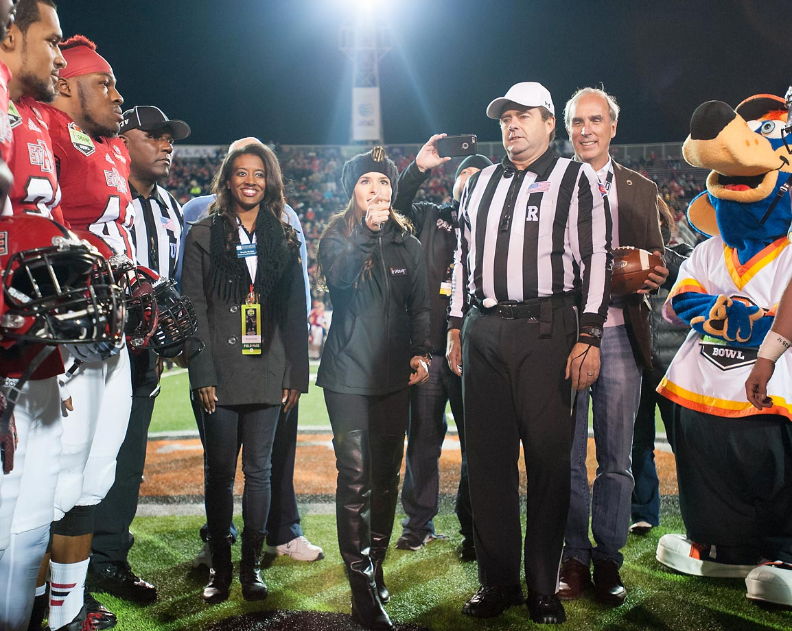 Race car driver Danica Patrick flips the coin prior to what appears to be a matchup between the Arkansas State Red Wolves and the Mascots.