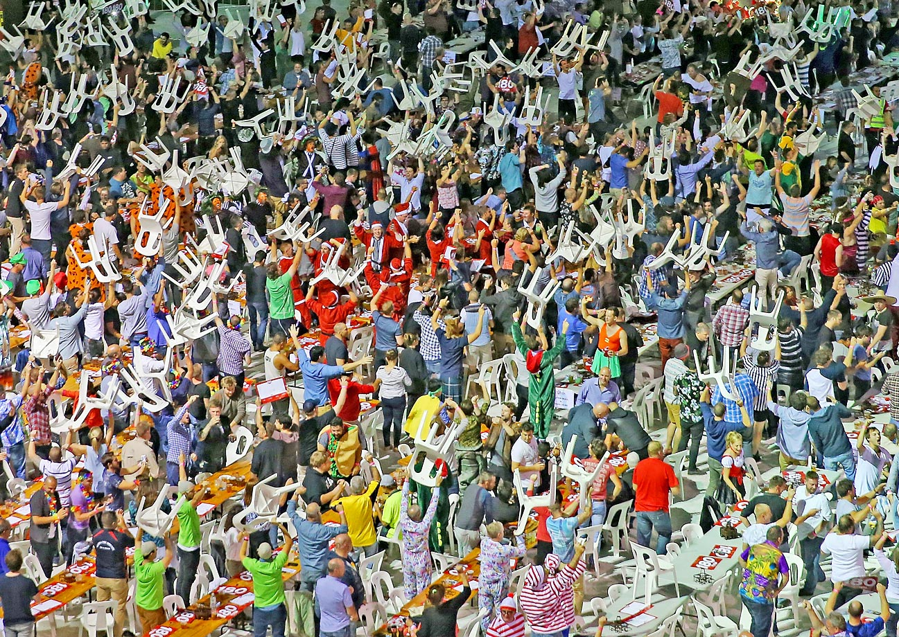 Fans in fancy dress raise chairs above their heads during the Invitational Darts Challenge at Etihad Stadium in Melbourne, Australia.
