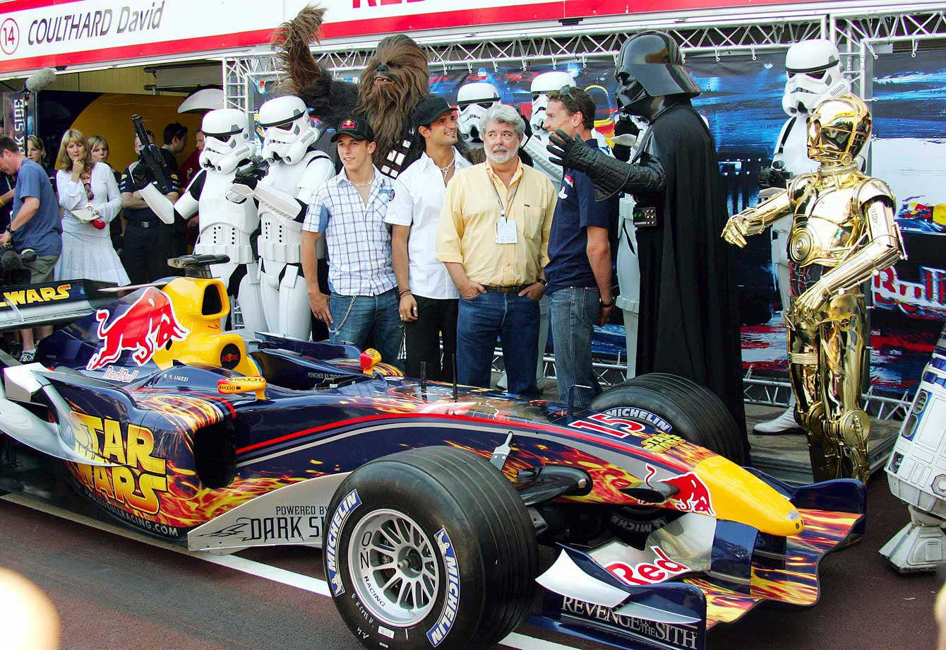 George Lucas and Red Bull Formula One driver David Coulthard, standing between Lucas and Darth Vader, pose behind the Red Bull race car on May 20, 2005 in Monte Carlo, Monaco.