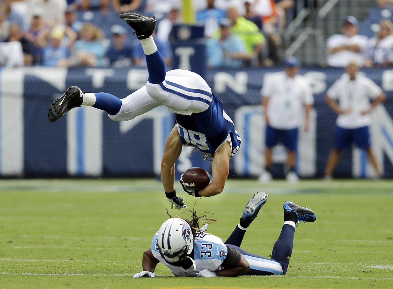 Coby Fleener of the Indianapolis Colts is upended by Michael Griffin of the Titans.