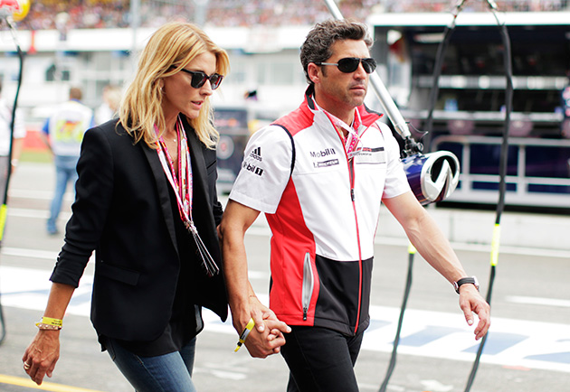 Driver and actor Patrick Dempsey walks past the Infiniti Red Bull Racing garage with his wife Jill Fink before the German Grand Prix at Hockenheimring on July 20, 2014 in Hockenheim, Germany.