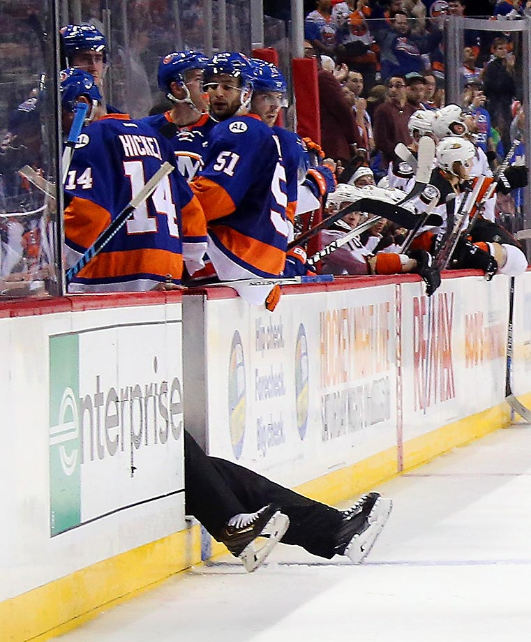Linesman Derek Nansen falls through the empty bench door during a game between the New York Islanders and the Anaheim Ducks at the Barclays Center.