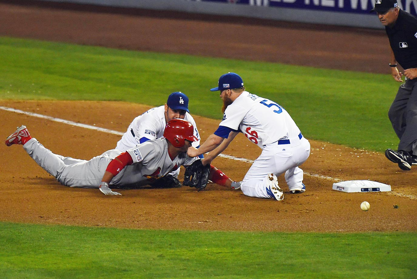 Oscar Taveras of the Cardinals dives back to first as Adrian Gonzalez and J.P. Howell cover.