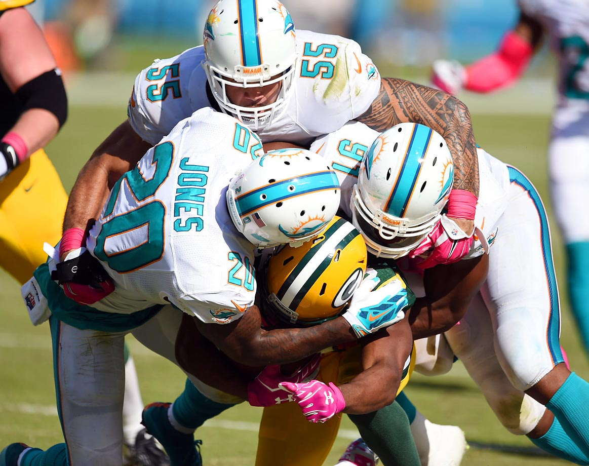 Miami Dolphins defenders Reshad Jones, Koa Misi and Cameron Wake take down Randall Cobb of Green Bay. The Packers won 27-24 on an Aaron Rodgers touchdown pass with six seconds left.