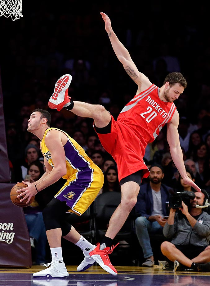 Donatas Motiejunas of the Houston Rockets falls over Larry Nance Jr. of the Los Angeles Lakers.