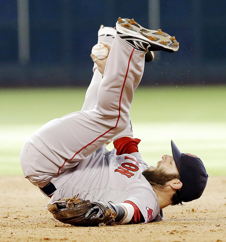 Boston Red Sox second baseman Dustin Pedroia holds up the ball while lying on his back after a double by Houston Astros' Jose Altuve in the eighth inning of a game on July 12, 2014, in Houston.