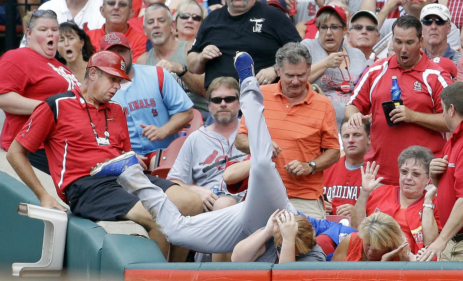 Chris Coghlan of the Chicago Cubs dives into the crowd to catch a foul ball hit by Tommy Pham of the St. Louis Cardinals.