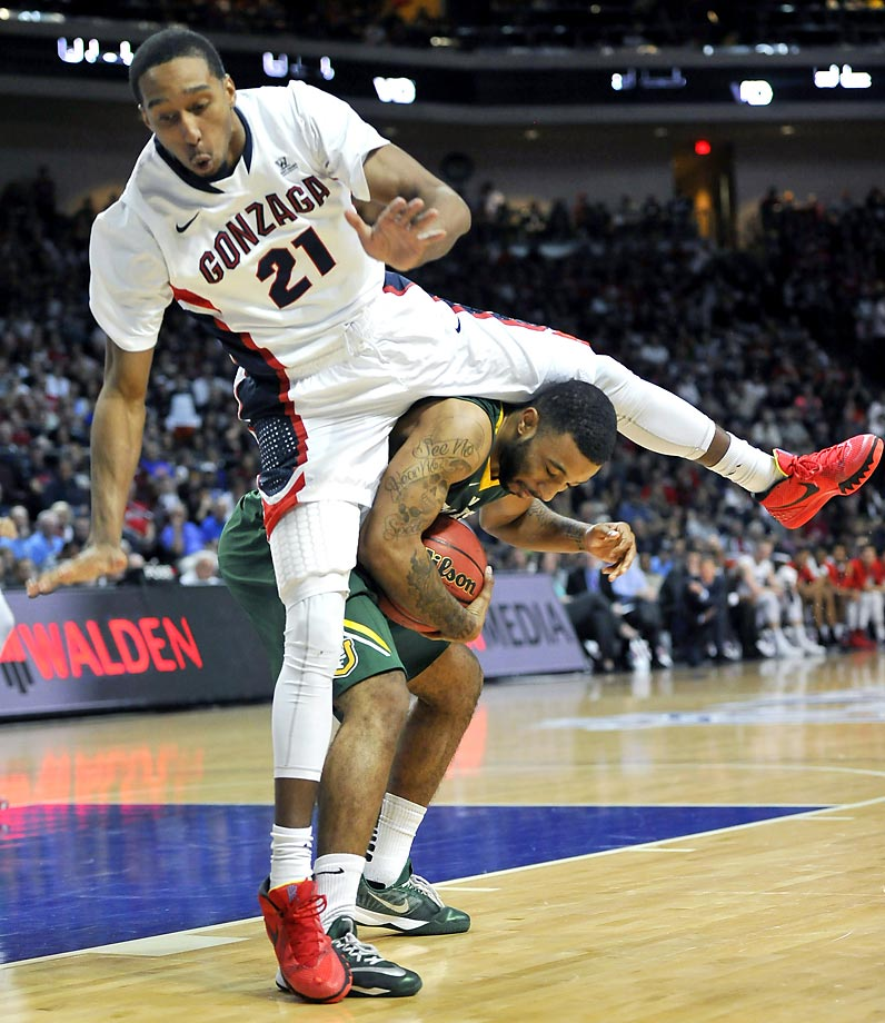 Eric McClellan of Gonzaga tries to hurdle Corey Hilliard of San Francisco. Gonzaga won 81-72.