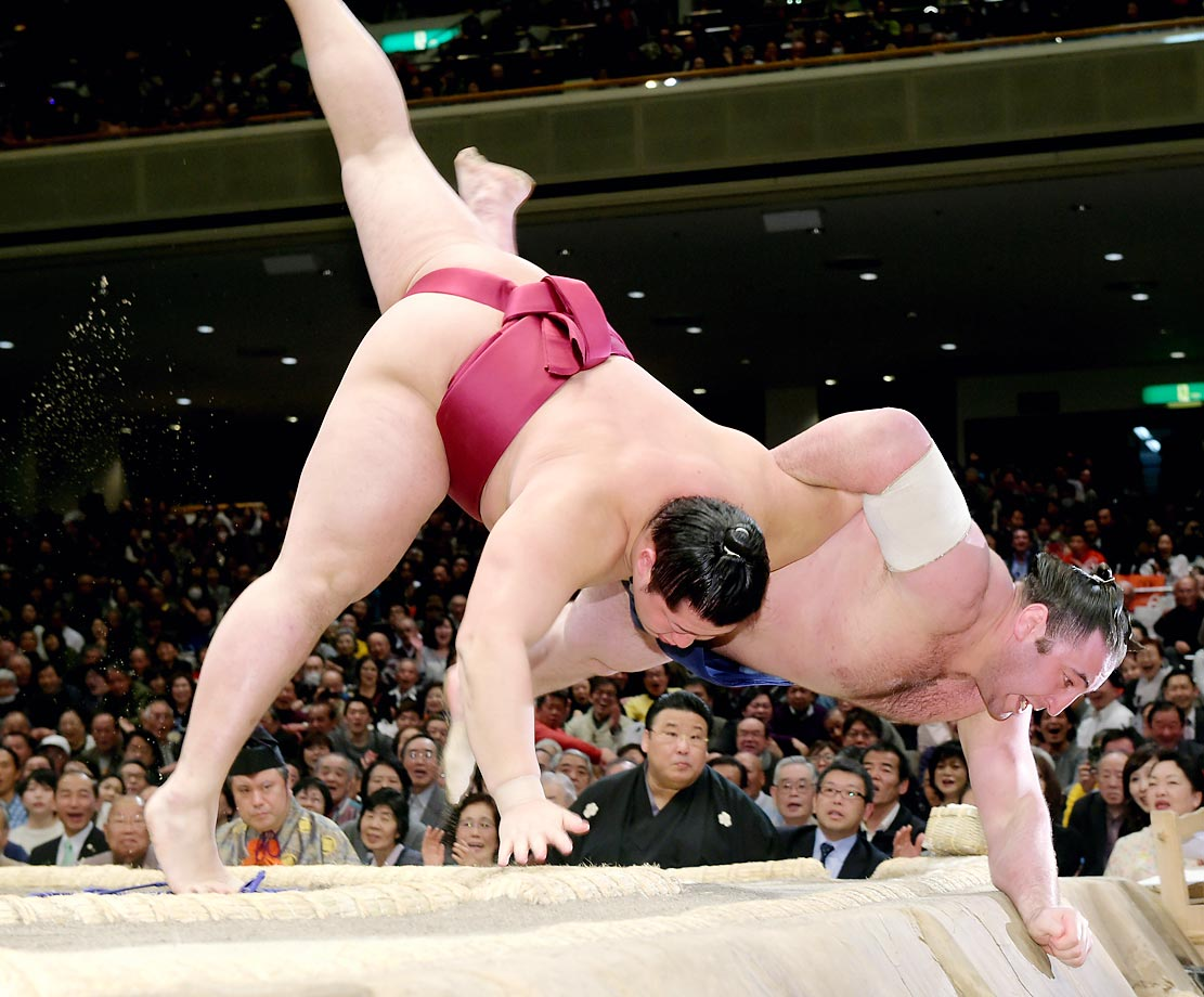 Endo (left) throws Tochinoshin to win during the Grand Sumo New Year Tournament at Ryogoku Kokugikan in Tokyo.