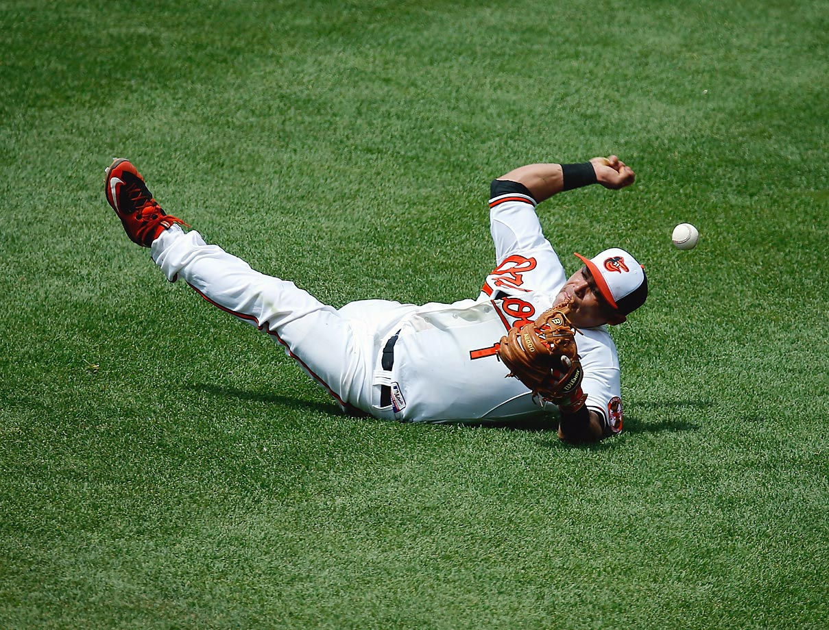 Everth Cabrera of the Baltimore Orioles tries to throw to first after knocking down an infield hit by Gordon Beckham of the Chicago White Sox.