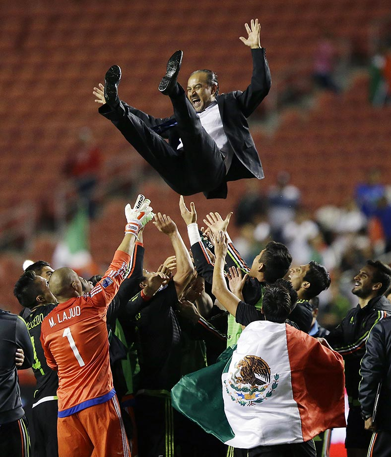 Raul Gutierrez, the head coach for Mexico, is thrown into the air after a qualifying championship match against Honduras.