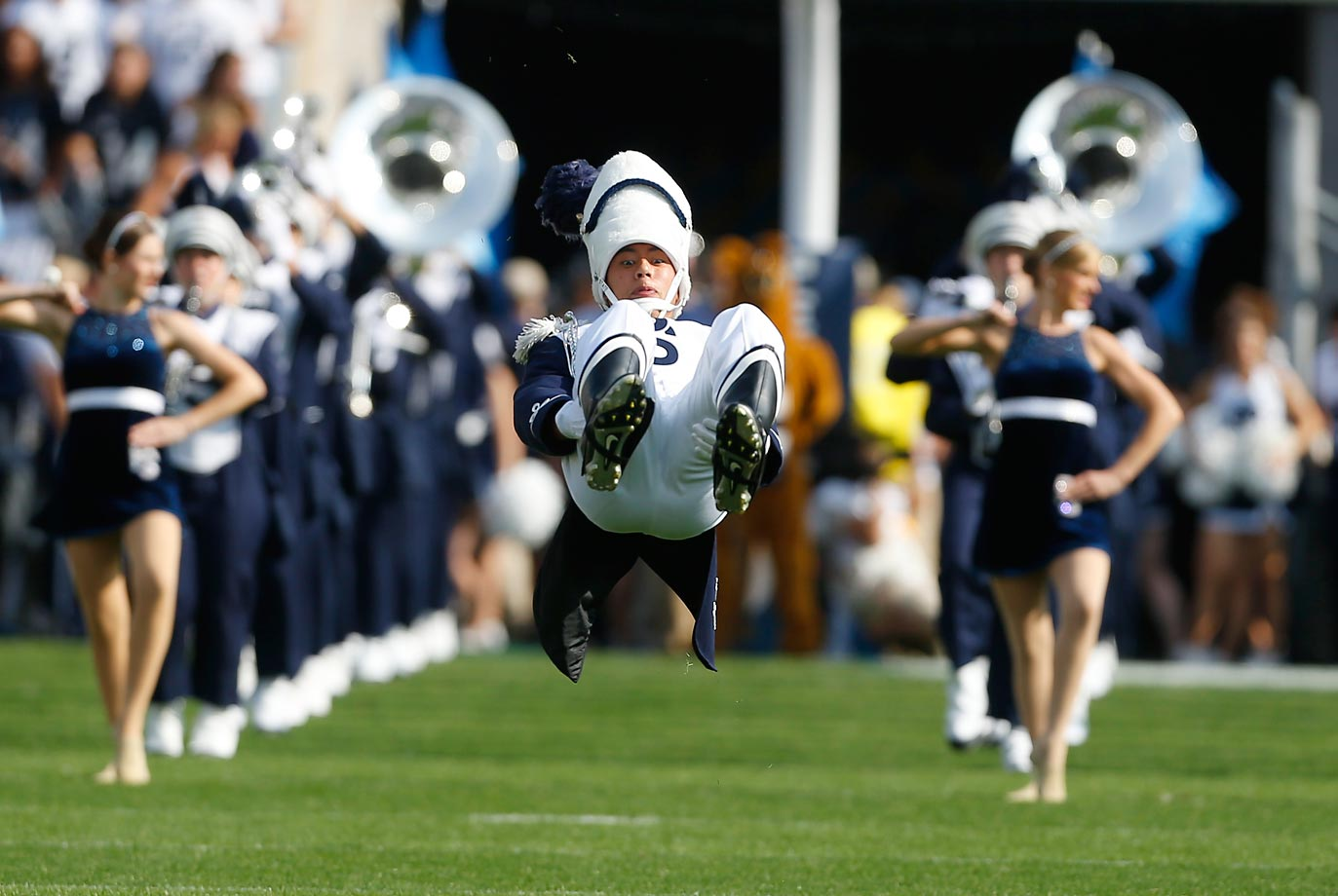 Drum Major Christopher Siergiej does a flip as he leads the Penn State marching band.