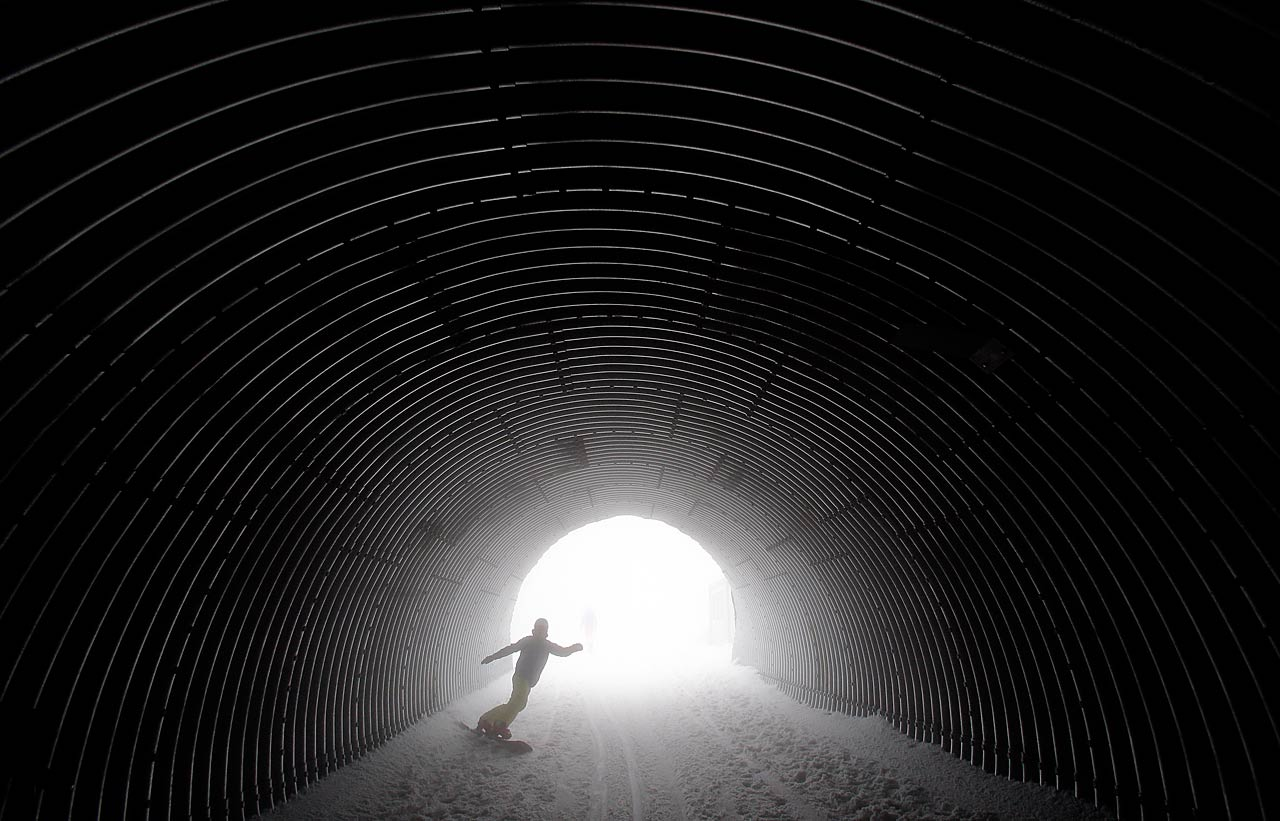 A snowboarder goes through a tunnel near the alpine skiing training slopes.
