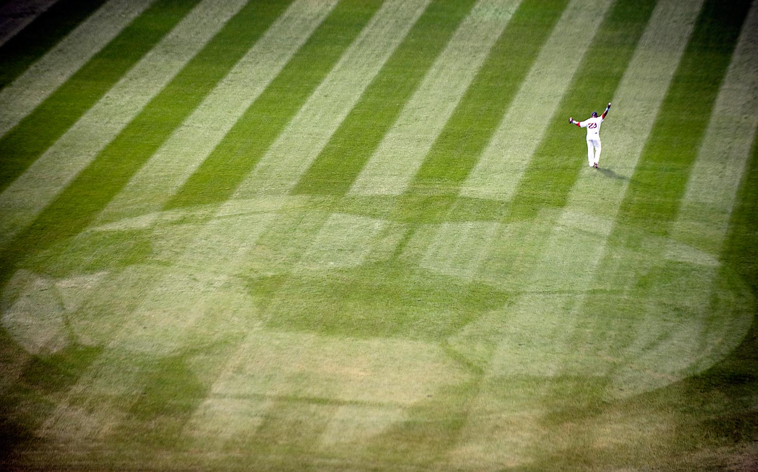 Mike Cameron of the Boston Red Sox on the field at Fenway before the start of a game against the Los Angeles Dodgers on June 20, 2010. An image of a soccer ball was mowed into the center field grass to promote a match between Scottish club Celtic FC and Portuguese club Sporting CP that is set to take place at Fenway Park on July 21st.