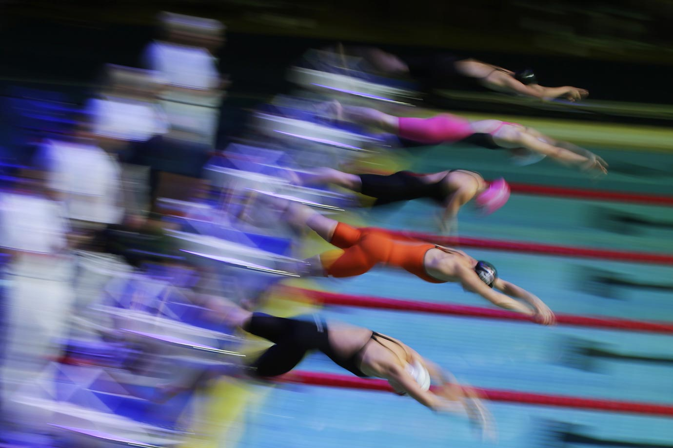 Swimmers leap off the starting blocks during the 100-meter freestyle final at the FINA Swimming World Cup.