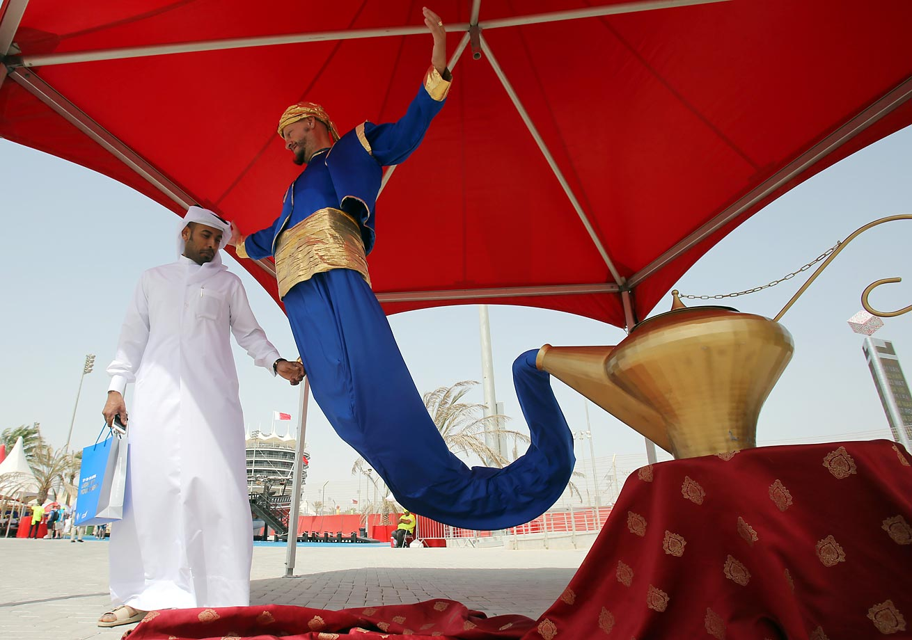 A Bahrain fan checks out a magic performer at the entertainment fun zone before the third practice session of the Bahrain Formula One Grand Prix.
