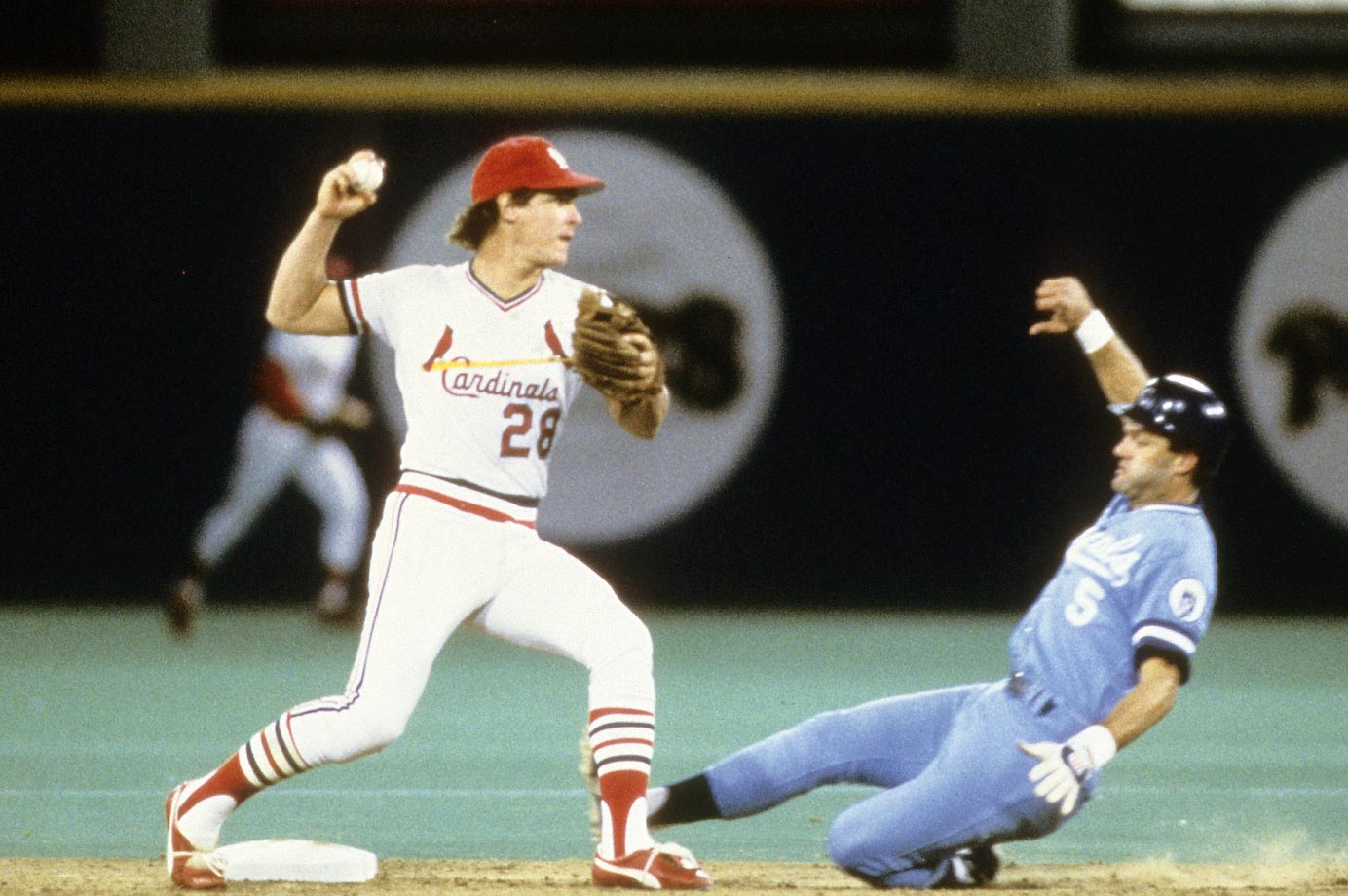 Cardinals infielder Tommy Herr throws to first base before George Brett slides into first.