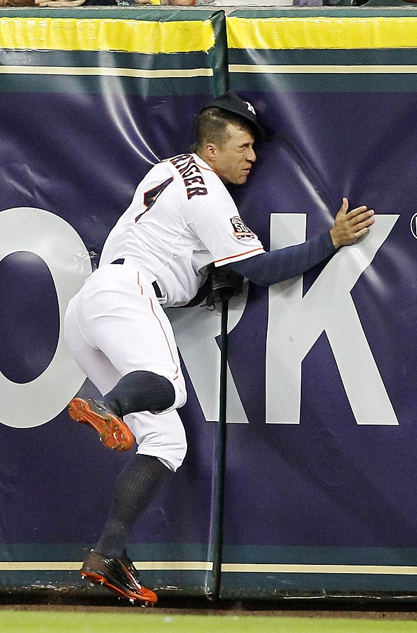 George Springer of the Houston Astros slams into the wall while making a catch against the Texas Rangers.
