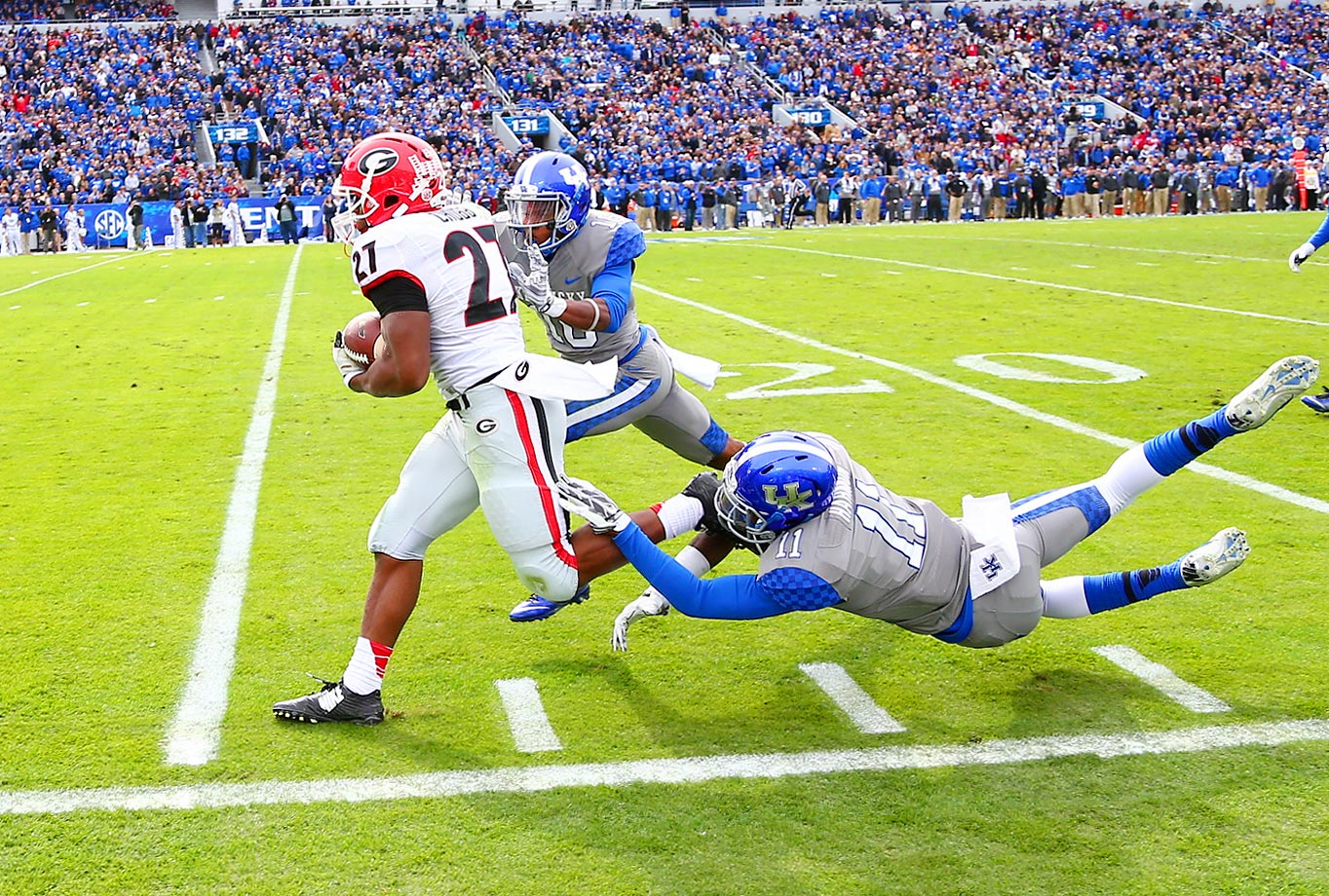 Nick Chubb of Georgia runs for yards against J.D. Harmon and Cody Quinn of Kentucky. Chubb finished with 170 yards and one touchdown in the Georgia win.