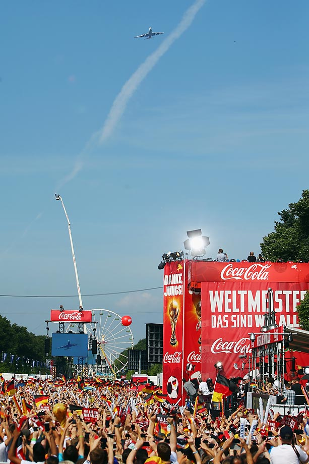 The airplane with the German national on board flies over the Fanmeile at Brandenburg Gate during the German team victory ceremony.