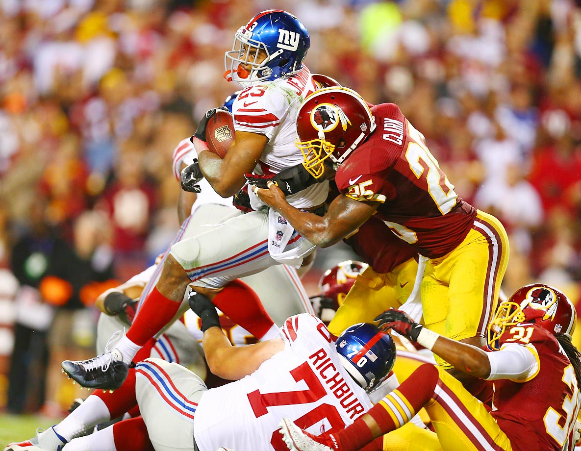 Giants running back Rashad Jennings is stopped by Redskins safety Ryan Clark.