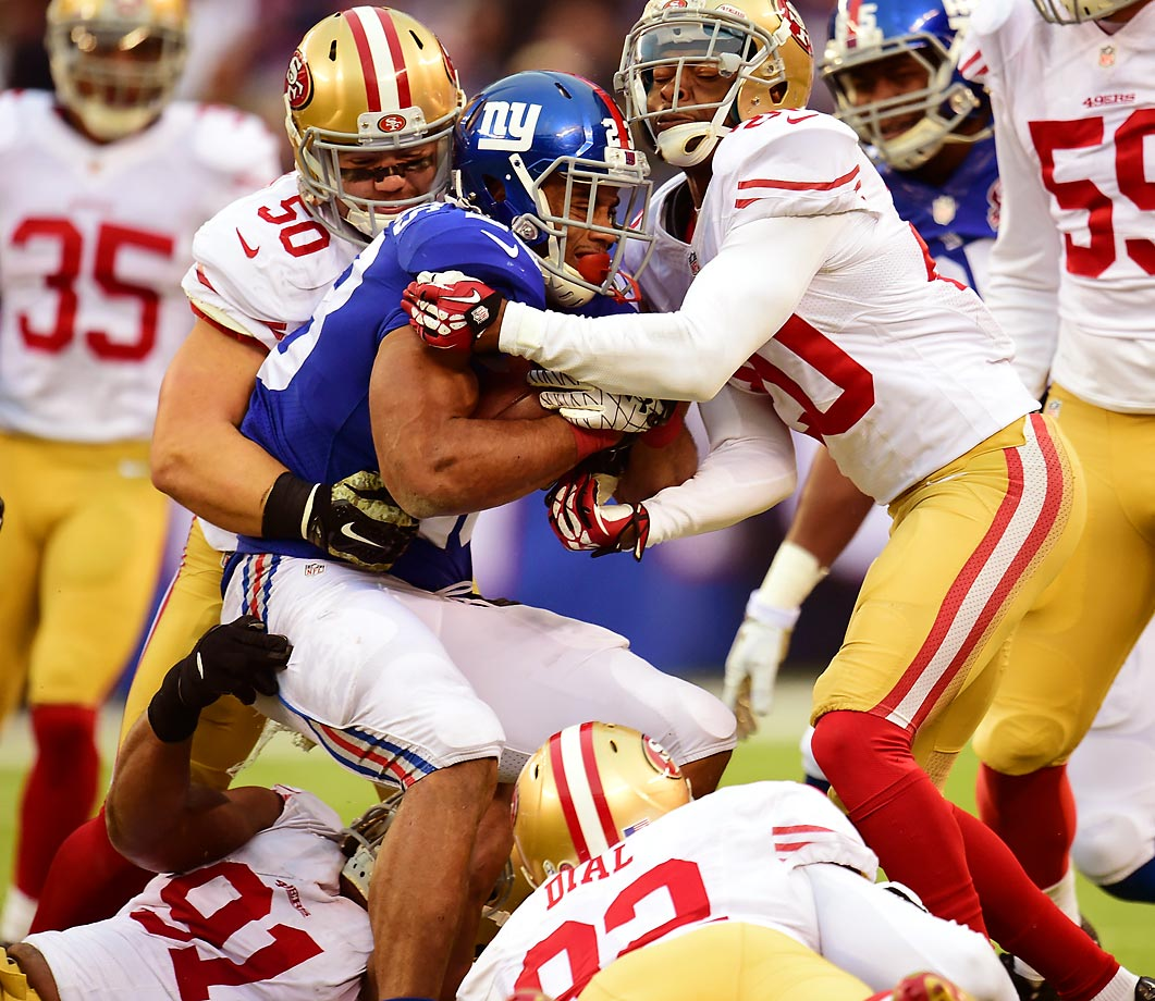 New York Giants running back Rashad Jennings stays on his feet as San Francisco 49ers defenders try to make a tackle. The 49ers defeated the Giants 16-10.