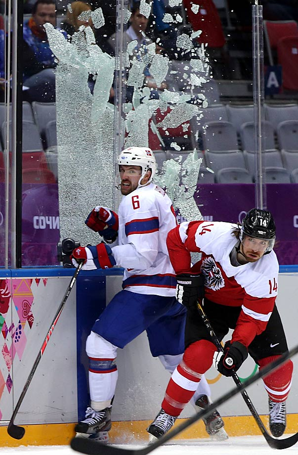 Andreas Nodl of Austria checks Jonas Holos of Norway to break the glass during Group B game.