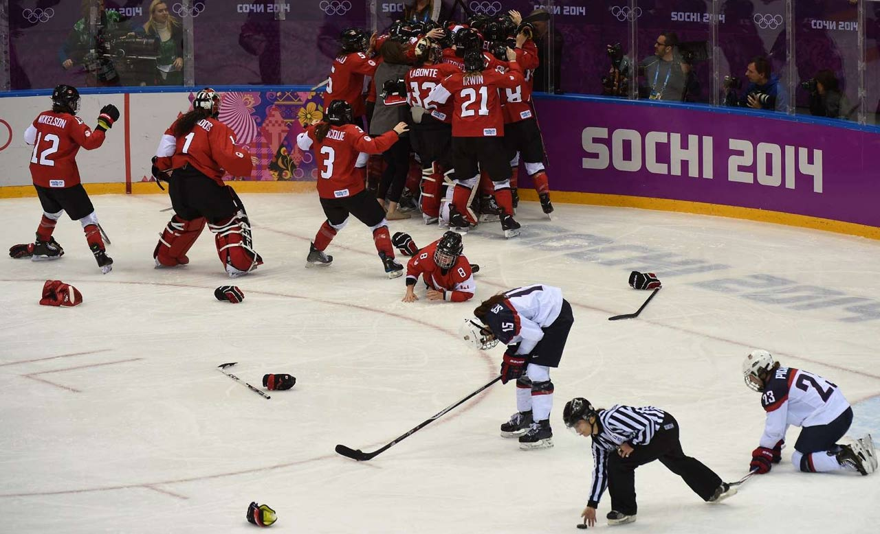 Team Canada celebrates it's game-winning score while the U.S. players show their disappointment in the 3-2 overtime loss.