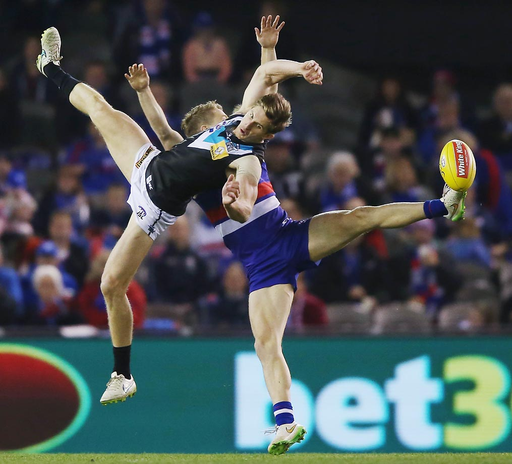 Hamish Hartlett of the Power and Lachie Hunter of the Bulldogs compete during a match between the Western Bulldogs and Port Adelaide Power in Melbourne, Australia.