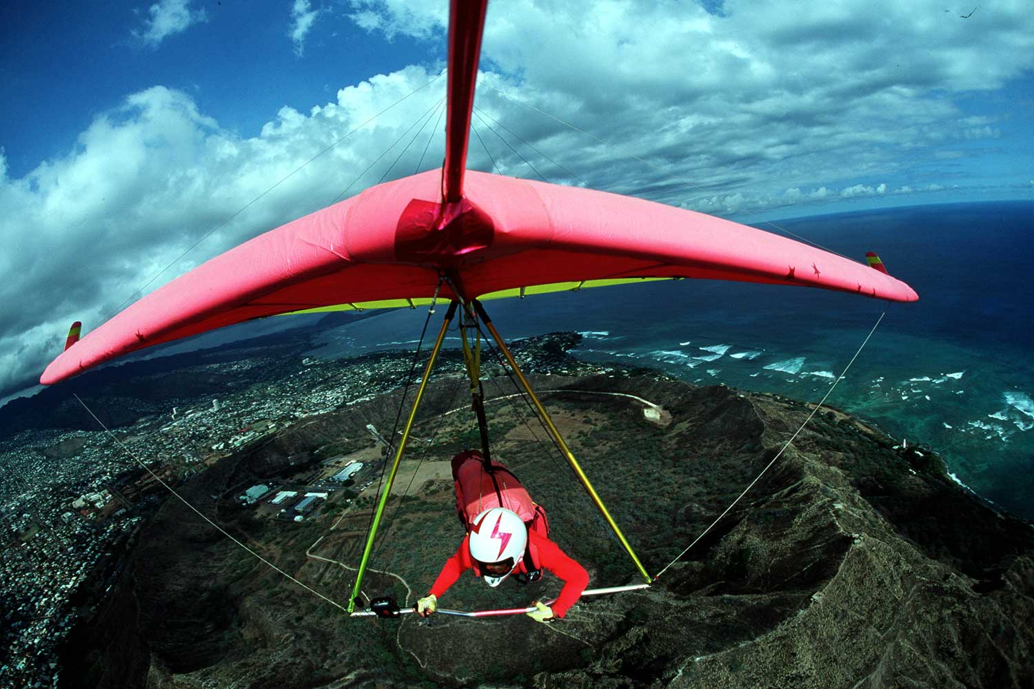 A hang gliding pilot steers his wing towards the landing zone while soaring above the ground below.