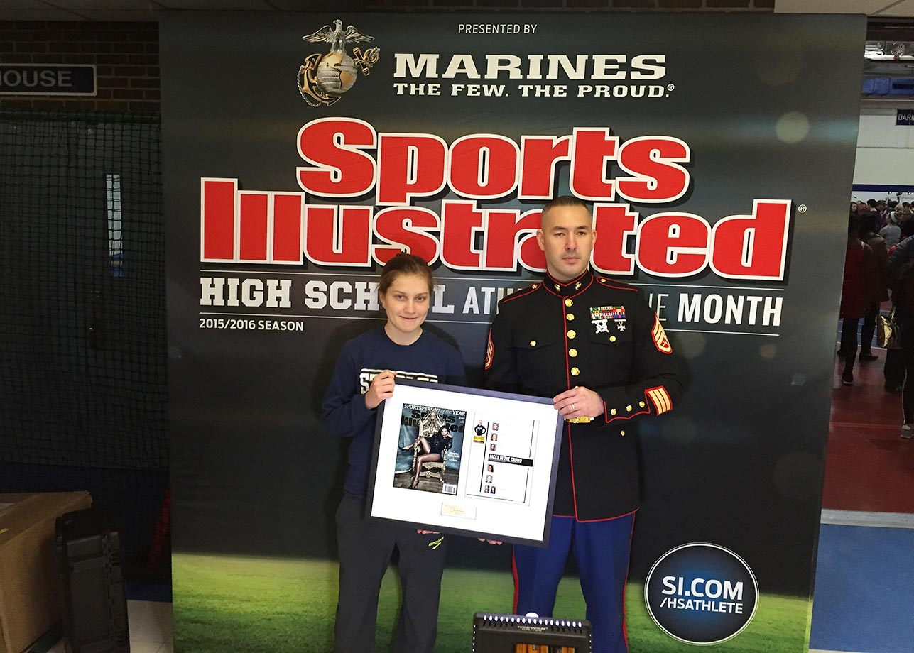 Hannah DeBalsi, who finished 5th at Foot Locker Nationals last year, being photographed with her award beside SSgt Jason Caldwell. The Stanford-bound senior athlete and SI High School Athlete of the Month for December appeared in the Dec. 21 issue of Sports Illustrated.