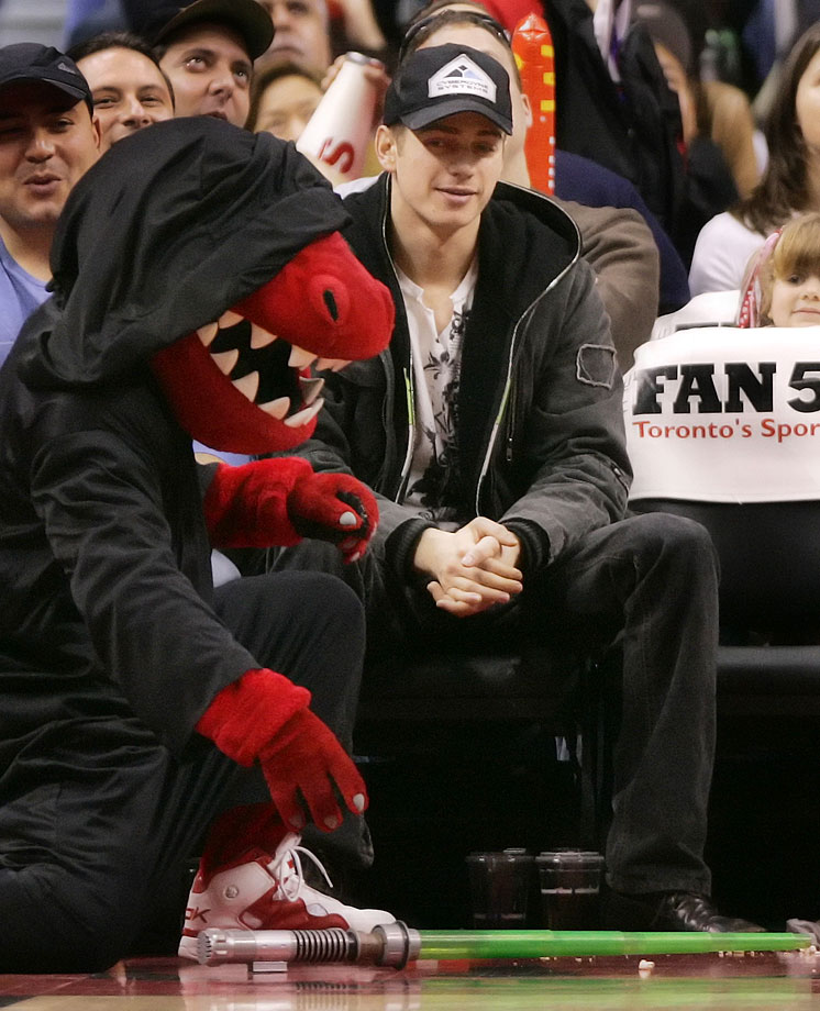 Hayden Christensen watches the Toronto Raptors mascot, dressed as a Sith, pick up a lightsaber during a time-out in the Raptors game against the Portland Trail Blazers on Dec. 10, 2006 at Air Canada Centre in Toronto.