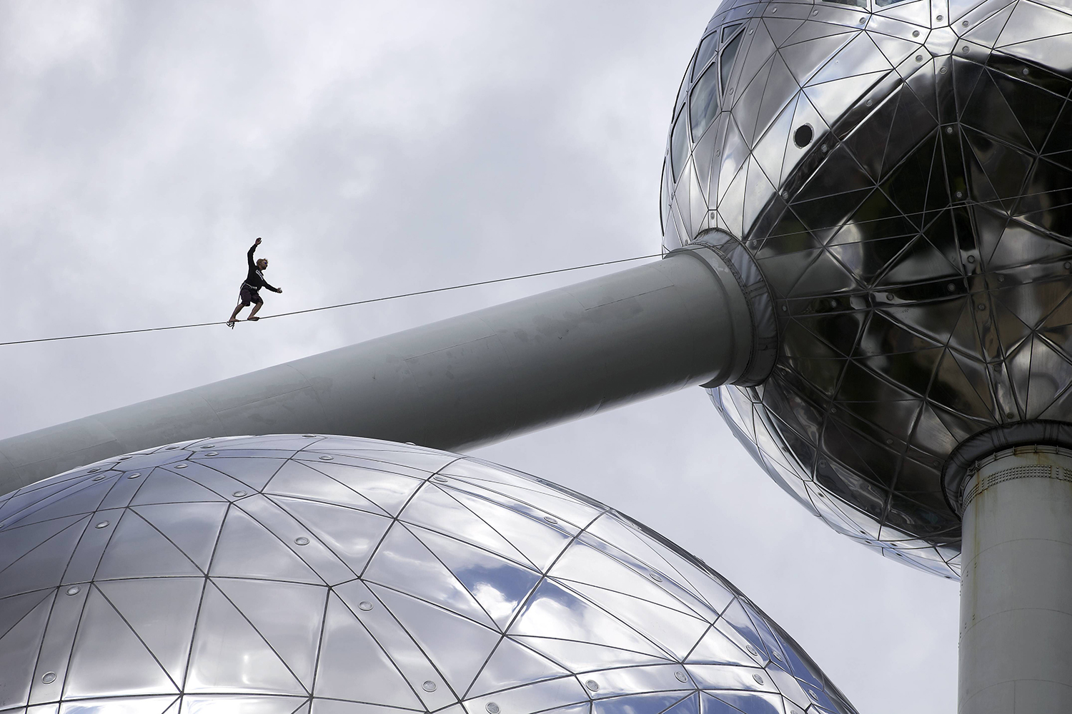 A person walks on a tightrope that connects the spheres of the atomium in Brussels.