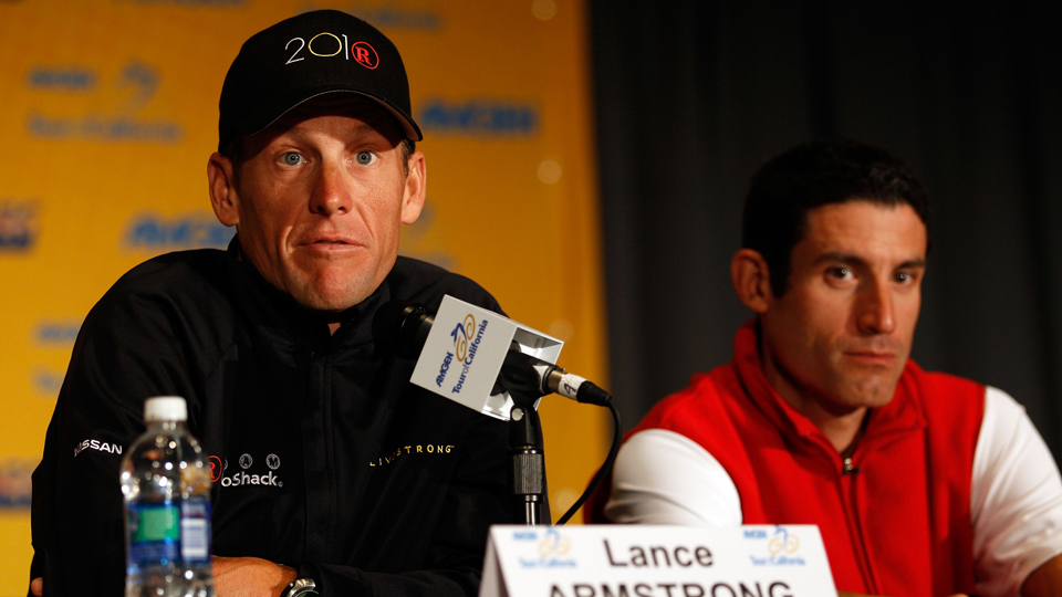 Lance Armstrong speaks to the media as his longtime teammate George Hincapie listens on during a press conference prior to the 2010 Tour of California.