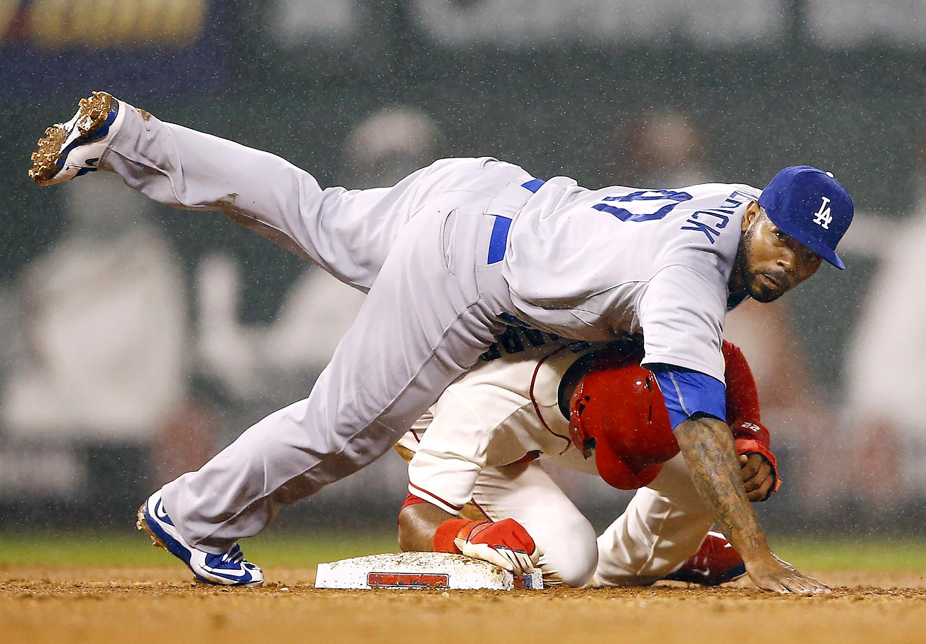 Howie Kendrick of the Los Angeles Dodgers turns a double play over Jason Heyward of the Cardinals.