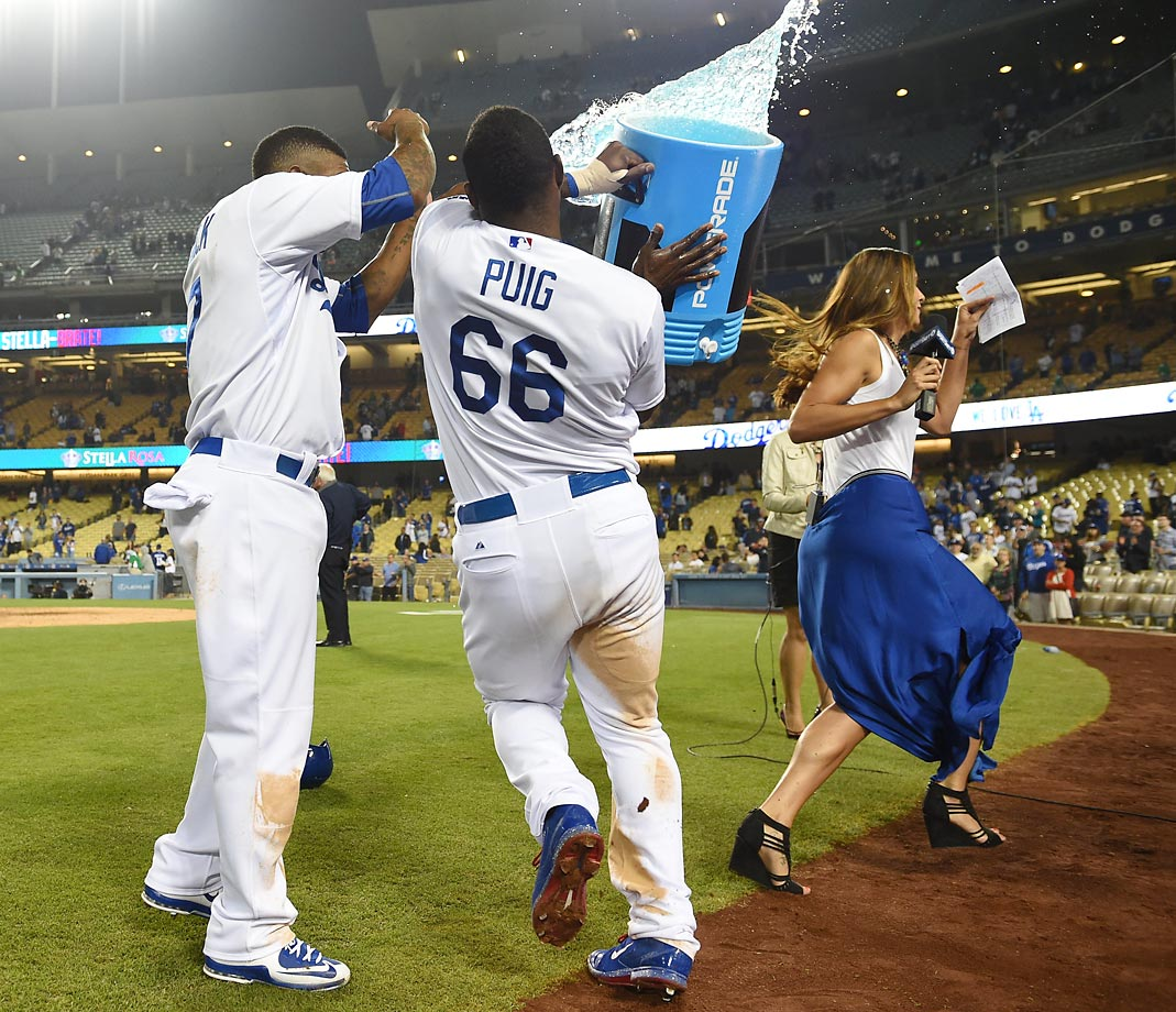 Yasiel Puig makes his way over to teammate Howie Kendrick to bestow a Powerade shower upon him following a Dodgers walk-off win on June 10.