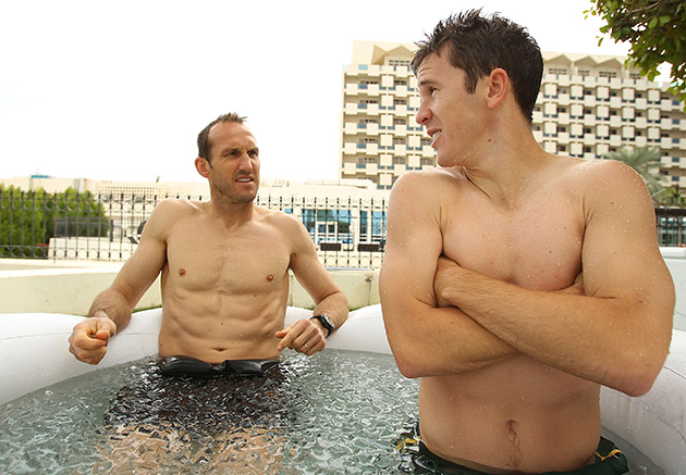 Mark Schwarzer and Matt McKay sit in an ice bath during an Australian Socceroos recovery session at the Marriott Hotel in Doha, Qatar.